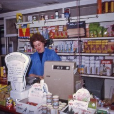 J Mace's mum behind shop counter, 1970s. | Photo: Edward Mace