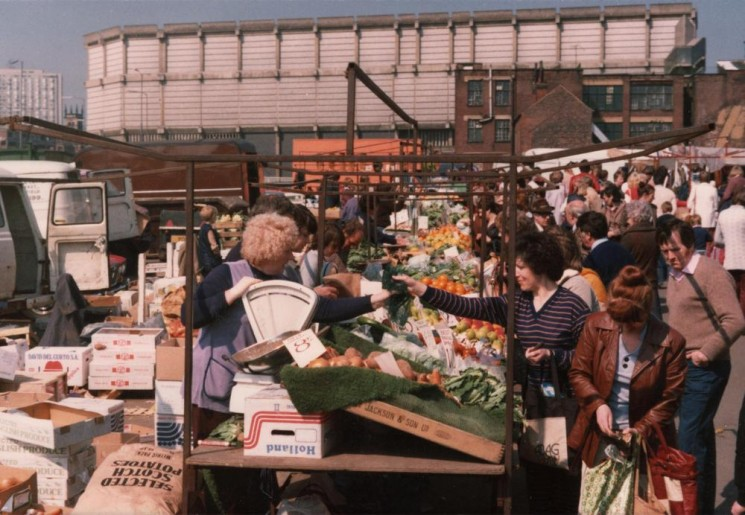 Fruit & veg stall at Moorfoot market. Moore St sub-station and Hallamshire Hospital in the background, May 1980 | Photo: Tony Allwright